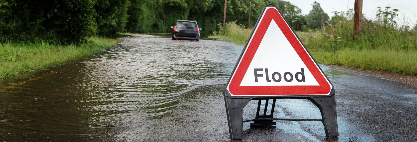 flooded road with warning sign banner image